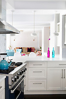 Open plan kitchen with white cupbopards