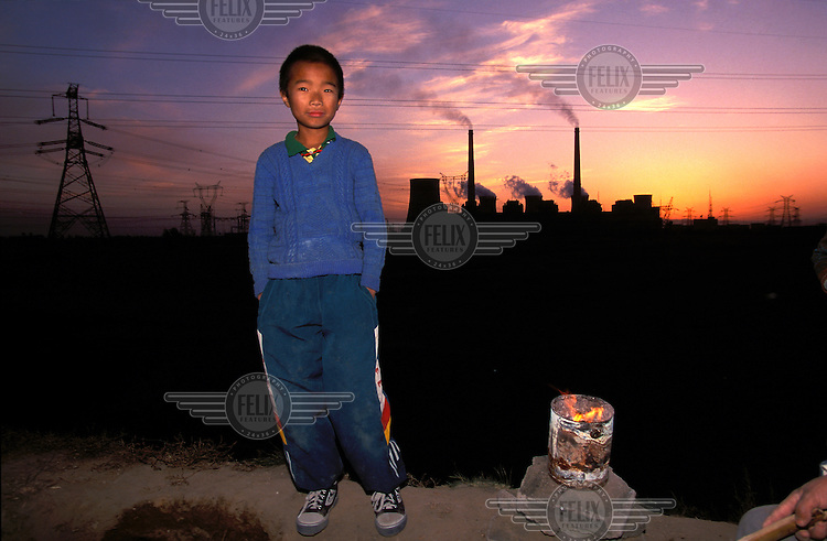 ©Mark Henley/Panos Pictures..China, Shanxi, Datong.Peasant child close to large power station.