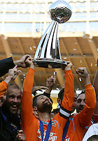 Houston captain Wade Barrett looks up at his refection in the base of the Alan I. Rothenberg trophy. The Houston Dynamo defeated the New England Revolution 2-1 in the finals of the MLS Cup at RFK Memorial Stadium in Washington, D. C., on November 18, 2007.
