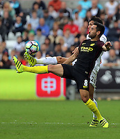 Ilkay Gundogan of Manchester City (FRONT) is challenged bt Jack Cork of Swansea City during the Premier League match between Swansea City and Manchester City at The Liberty Stadium in Swansea, Wales, UK. Saturday 24 September 2016