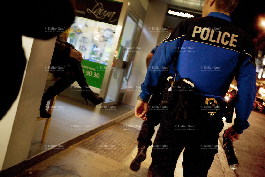 """Switzerland. Geneva. Two police officers at night on the streets of the Paquis neighborhood, known for its nightlife and Red-light district. The policeman (R) holds a pepper spray in his hand. Street prostitution. Most of the prostitutes work in the streets. Prostitution is often referred to as """"the world's oldest profession"""". Both policemen are wearing a ballistic vest, bulletproof vest or bullet-resistant vest which is an item of personal armor that helps absorb the impact from knives, firearm-fired projectiles and shrapnel from explosions, and is worn on the torso. Soft vests are made from many layers of woven or laminated fibers and can be capable of protecting the wearer from small-caliber handgun and shotgun projectiles, and small fragments from explosives such as hand grenades. Pepper spray, also known as OC spray (from """"Oleoresin Capsicum""""), OC gas, and capsicum spray, is a lachrymatory agent (a chemical compound that irritates the eyes to cause tears, pain, and even temporary blindness) used in policing. Its inflammatory effects cause the eyes to close, taking away vision. This temporary blindness allows officers to more easily restrain subjects. 17.03.12 © 2012 Didier Ruef"""