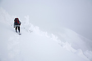 Franconia Notch State Park - Snowshoer following the Rim Trail on the summit of Cannon Mountain in whiteout conditions during the winter months in the White Mountains, New Hampshire USA