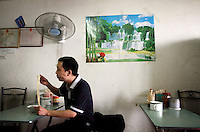 A man eating noodles in a restaurant near Dongting Lake, Hunan Province. Dongting Lake has decreased in size in recent decades as a result of land reclamation and damming of the Yangtze. China. 2010