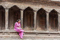 Nepal, Patan.  Young Nepali Woman Sitting on Edge of Temple, Tika on her Forehead.
