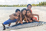 i-Kiribati children posing for the camera with a fish in a village on the island of Kiritimati in Kiribati