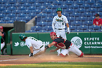 Tulane Green Wave Collin Burns (2) slides home safely beating the tag of catcher Dylan Post (31) during a game against the Houston Cougars on May 25, 2021 at BayCare Ballpark in Clearwater, Florida.  Tulane defeated Houston 4-1 in the opening game of the American Athletic Conference Tournament.  Chase Engelhard (5) looks on.  (Mike Janes/Four Seam Images)