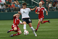 USWNT's Megan Rapinoe(15), ctr controls the ball as Canada's Diana Matheson (8), left slides in for a tackle and Cat Whitehill (4) pursues. The U.S. Women's National Team defeated 1-0 in a friendly match at Marina Auto Stadium in Rochester, NY on July 19, 2009. Abby Wambach of the USWNT scored her 100th career goal in the second half..