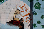 A Palestinian walks past a coronavirus-inspired mural along a street in Gaza City on April 22, 2021 amid the coronavirus disease (COVID-19) outbreak. Palestinians welcomed the Muslim fasting month of Ramadan under the shadow of economic difficulties caused by the Israeli blockade and the coronavirus pandemic. Nineteen people have died of the coronavirus disease in Palestine in the last 24 hours and 1652 new cases were recorded, according to the daily report on the disease. Health Minister Mai Alkaila said 11 of the dead and 1179 of the new cases were in the Gaza Strip. Photo by mohammed salem