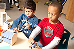Education preschool 3-4 year olds two boys sitting side by side playing with small dolls and furniture, talking and vocalizing as they pretend