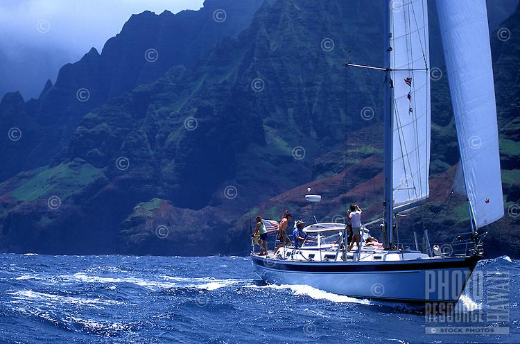 Family sailing a 48 foot sailboat down the rugged Na Pali Coast, Kauai, Hawaii
