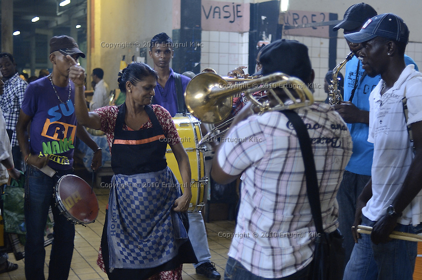 A lady fish seller dances in the middle of street band while they are playing for sellers and shoppers in the Central Market of Paramaribo. This is a tradition in Suriname and the bands plays at different locations, places before  important days, festive start.....End of year 2010 celebrations on the streets of Paramaribo. Suriname is one of biggest consumer in South America that using firecrackers, fireworks ( also locally known as pagara ) for celebrations, especially for end of every years and also beginning of every new Chinese Years.