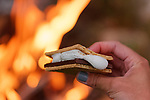 A young woman holding a s'more with a blazing campfire in the background.