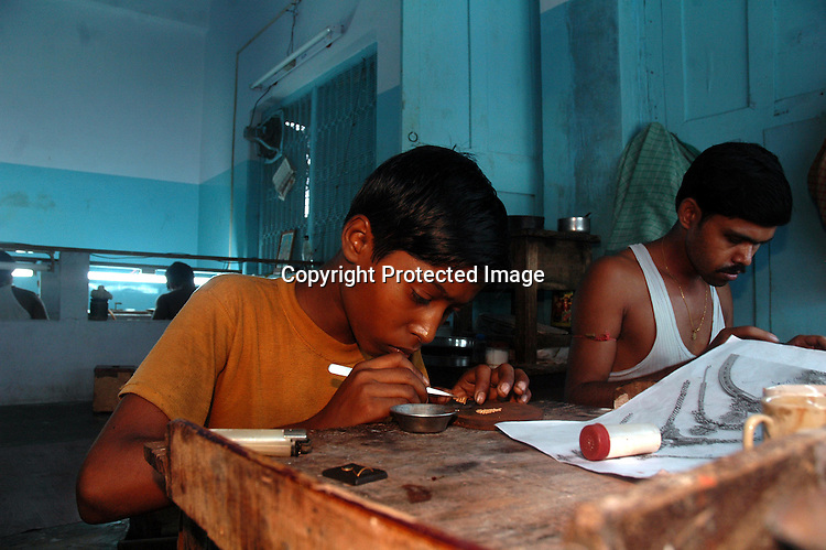 An Indian young boy working minutely with golden balls to make an expensive ornament. Kolkata, India  6/13/2007  Arindam Mukherjee