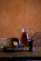 A jug of loganberry juice and an apple on a wooden chopping board on the kitchen table