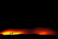 Spectators on horizon watching lava flow from Kilauea volcano, Hawaii Volcanoes National park, Big Island
