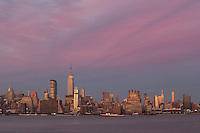 WEEHAWKEN, NJ - JULY 4:  The setting sun casts a magenta glow on the sky over the Empire State Building and Manhattan skyline, as seen from Weehawken, NJ, prior to the annual Macy's Fourth of July fireworks on Saturday, July 4, 2009.
