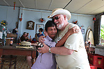 """Nguyen Tan Hoa, 55, embraces Marine Corps veteran Bill Taylor at Hoa's Place guesthouse on China Beach, south of Da Nang, Vietnam. Nguyen was 10-years-old when a Marine unit known as a Combined Action Platoon moved into his village, about 25 miles southwest of Da Nang. He soon began spending much of his time with the Americans and remembers it as the most profound experience of his life. """"Whatever they got, I got,"""" he recalls. """"We shared the poncho together. We shared the cigarette together. We shared everything."""" Nguyen occasionally hosts groups of returning veterans for lunch at the guesthouse. Taylor, 65, of Dyer, Ind., served with 1st Battalion, 3rd Marine Regiment from 1967 to 1968. This was his first time back in Vietnam since the war. """"I've already lost it a couple of times,"""" he said. """"But it's been a refreshing feeling. I'm here with my brothers."""" April 27, 2012."""