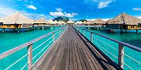 Overwater bungalows and wooden bridge with Mount Otemanu background in Bora Bora honeymoon destination, near Tahiti, French Polynesia, Pacific Ocean