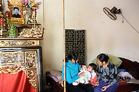 Vietnam. Ha Tay province. Three generations. Grandmother, mother and her two children. The older boy is kissing his younger sister. Religious family altar (L) for the loving and dead parents who passed away. Lai Xa is a typical hamlet (village) and is part of the Kim Chung commune located 15 km west of Hanoi. 06.04.09 © 2009 Didier Ruef