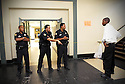 New Orleans police officers ask a student to tuck in his shirt at John McDonogh High School, New Orleans, Wed., Oct. 18, 2006. .(Cheryl Gerber for New York Times)..