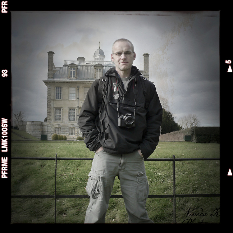 Mark standing with a camera in front of stately home.