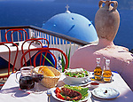 Greece; Cyclades; Santorini; set table with greek food in front of a blue and white church