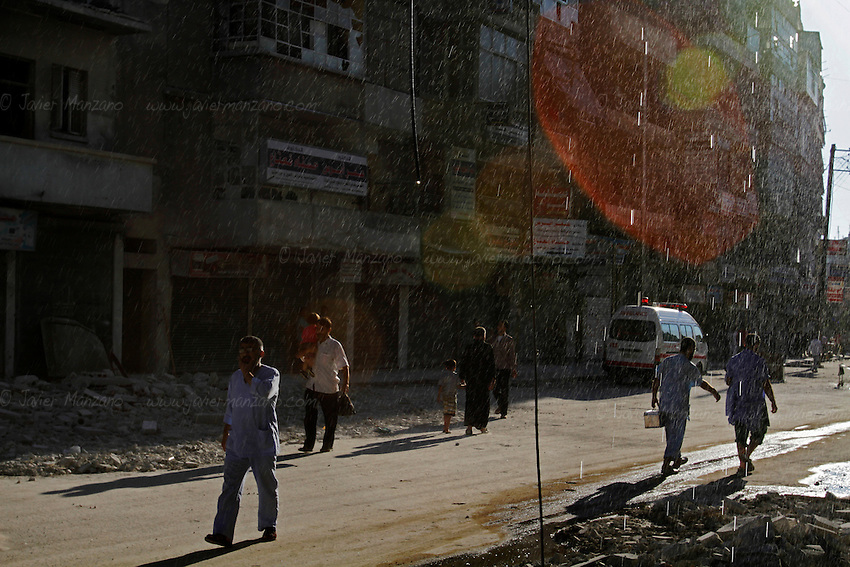 Doctors and civilians walk by the entrance to a small clinic in the heart of the Sha'ar neighborhood of Aleppo - water drips from a damaged water pipe as a result of one of the latest attacks on this small hospital (the clinic has been targeted over a dozen times). ..© Javier Manzano