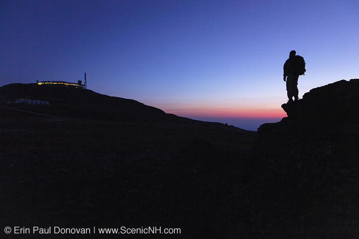 A hiker takes in the view of Mount Washington at sunset from a rocky outcrop known as Ball Crag along the Nelson Crag Trail in the White Mountains, New Hampshire.