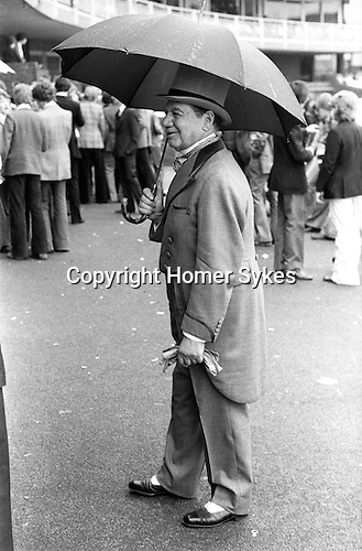 St Johns Wood, London. England. 1975<br /> At the Eton v Harrow annual cricket match at Lords. An old Etonian wears a grey topper and matching velvet trimmed morning suit, with a wing collared shirt. He sports a cotton spotted cravat, buckskin grey gloves and black and white two-tone shoes. Surely, the height of sartorial elegance?