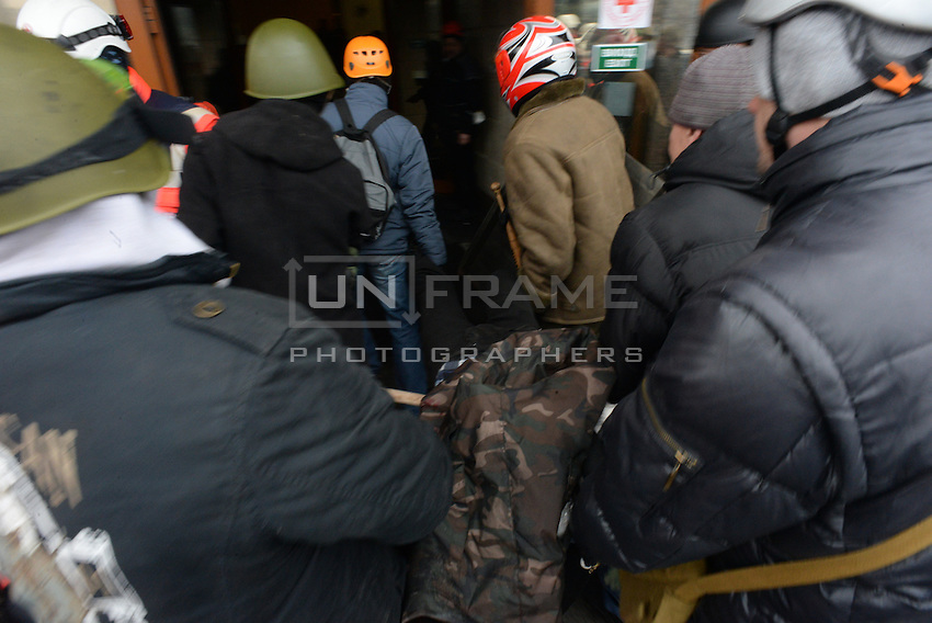 Protesters help wounded people and lift them into a makeshift clinic where red cross medics treat them as they can do.  Kiev, Ukraine