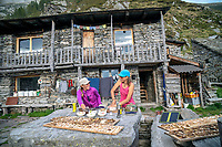 Two hikers enjoying the spread of food at the Capanna Nimi, while hiking the Via Alta Via Maggia, a difficult week long trek from Locarno to Broglio, Switzerland