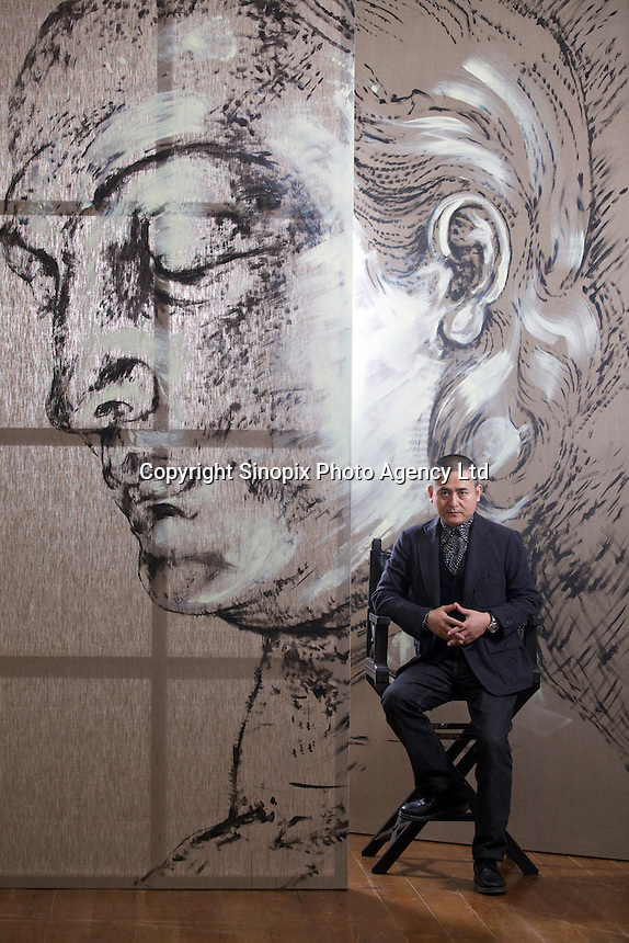 """Zeng Fanzhi, China's renowned contemporary artist, poses for pictures between an unfinished painting in his Beijing studio on 9th November, 2012, China. Zeng gained the title of """"Number One"""" Chinese artist in terms of auction price in 2009.<br /> <br /> PHOTO BY RICKY WONG / SINOPIX"""