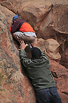 Father helping son climb a rock wall in Arches National Park, Moab, Utah, USA. .  John offers private photo tours in Arches National Park and throughout Utah and Colorado. Year-round.