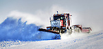 A plow truck clears snow from an ice road