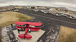 Open House at the WInnemucca Airport as photographed using the DJI Phantom quadcopter drone and GoPro Hero 3 camera from above the event. <br /> <br /> Aircraft on the ramp–red Waco  UPF-7 biplane was a trainer originally built in the late 1930s just prior to WWII