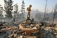 X.POY.3.1023.jl.jpg/photo Jamie Scott Lytle/A birdbath with a statue remains in the ashes of the  Webb property located at 3700 block of Mission Road burned to the ground Tuesday morning.