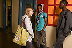 Education High School corridor between classes female student talking with two male students horizontal