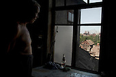 Mariupil, Ukraine.July 29, 2005..A view of the factory from a house across the river from the steel factory ?Azovstal?. Petr Soroka, 51 y.o. A sailor in past he has lived in Mariupil for 30 years, he was born in Kiev. He has a wife and a son. He worked at the sea port. ..The steel factory was built at 1933. Now it has 20,000 workers and producing 5,000 tons of steel every day. It works 24/7 and exports to different countries.