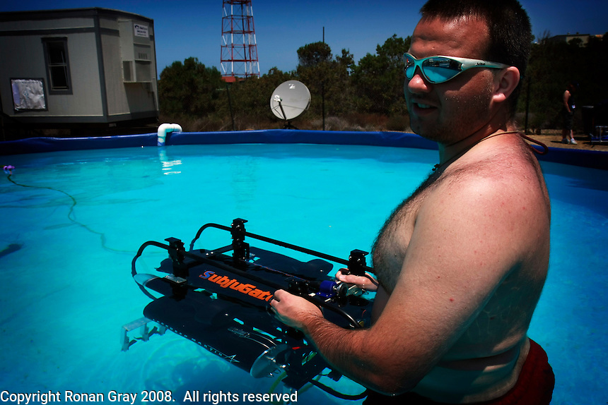 """TRANSEC Sonar Test Basin, Point Loma, San Diego, CA, USA. Friday, August 1 2008.  Tom Fenney of the Florida Institue of Technology holds his teams Autonomous Underwater Vehicle """"Subjugator"""" in  a test pool next to the TRANSDEC pool at the site of the 2008 AUVSI underwater vehicle competition."""