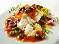 cod fillet with a ragu and caper sauce being cut into