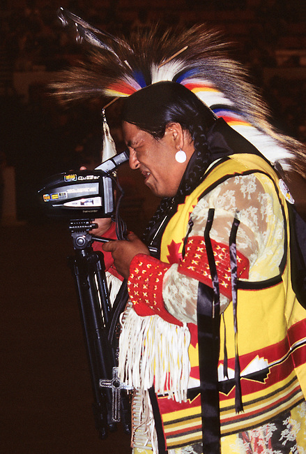 Traditionally dressed Native American man video tapes grand entry dancers during the Red Earth Indian Festival and Pow Wow in Oklahoma City, OK.