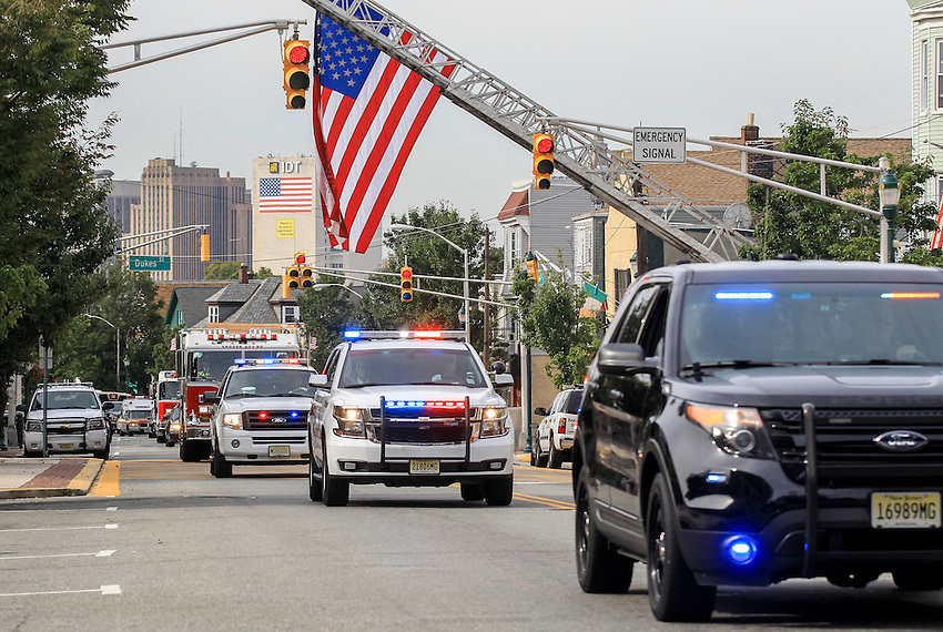 The procession makes its way beneath a giant American flag on Kearny Avenue en route to St. Cecilia's Church for the funeral for Manasquan volunteer firefighter Dan McCann. McCann died last week after a fire department training exercise.  9/21/16  (Andrew Mills   NJ Advance Media for NJ.com)