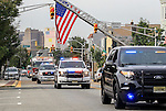 The procession makes its way beneath a giant American flag on Kearny Avenue en route to St. Cecilia's Church for the funeral for Manasquan volunteer firefighter Dan McCann. McCann died last week after a fire department training exercise.  9/21/16  (Andrew Mills | NJ Advance Media for NJ.com)