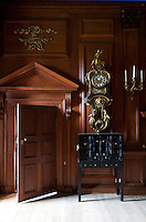 An 18th century French wall clock hangs above a cabinet of curiosities in the ante-room