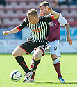 Pars' Andrew Geggan holds off Arbroath's Bobby Linn.