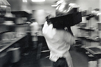 Blur of busboy walking with tray of dishes on shoulder in kitchen.