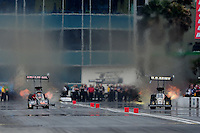 Mar. 11, 2012; Gainesville, FL, USA; NHRA top fuel dragster driver Terry McMillen (left) races alongside Tony Schumacher during the Gatornationals at Auto Plus Raceway at Gainesville. Mandatory Credit: Mark J. Rebilas-