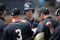Bruce Steel (17) of the Wake Forest Demon Deacons is congratulated by his teammates after scoring a run against the Miami Hurricanes at Wake Forest Baseball Park on March 22, 2015 in Winston-Salem, North Carolina.  The Demon Deacons defeated the Hurricanes 10-4.  (Brian Westerholt/Four Seam Images)