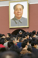 China. Province of Beijing. Beijing. Tiananmen Square. Picture of the communist leader and chairman Mao Zedong. The photography is fixed on the wall near the entrance of Tian'anmen Gate. A policeman checks the crowd on the feast of the first of may.  © 2004 Didier Ruef