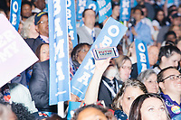 """A person holds an iphone with a mock campaign sign reading """"Putin / Trump"""" in the crowd as President Barack Obama speaks at the Democratic National Convention at the Wells Fargo Center in Philadelphia, Pennsylvania, on Wed., July 27, 2016."""